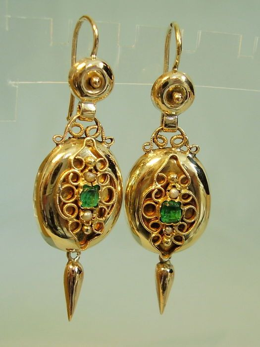 Antique earrings made from 585 yellow gold = 14 kt finished and hallmarked. Earrings with large hooks and moveable oval suspension with filigree editions in whose centre is a quadrilaterally facetted emerald-green colour stones as well as small river pearls Underneath a moveable lance-shaped suspension. Length 4.5 cm, width 1.4 cm, weight 4.7 g. Very well preserved, very rare in this high-value creation from 14 kt gold.  Shipped in new jewellery case. Depicted jewellery boxes or holders are…