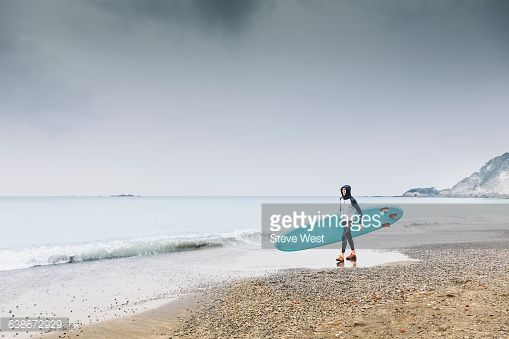 Athletic young man walking on the beach holding a Stand Up Paddleboard looking at a calm ocean
