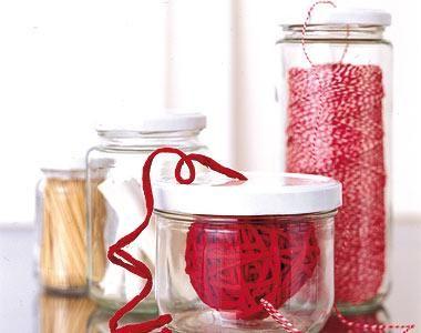 Die Gläser zuerst gut spülen und trocknen. Dann mit einem Pikser für Kondensmilchdosen oder mit einem starken Metallnagel und einem Hammer in den Deckel ein Loch bohren. Das muss so groß werden, dass der Faden hindurch passt. Die spitzen Kanten an der Deckelunterseite mit Schmirgelpapier glätten. Dann die Außenseiten der Deckel mit Lackfarbe besprühen und trocknen lassen. Kordelknäuel ins Glas legen, Faden durch das Loch im Deckel ziehen - fertig.
