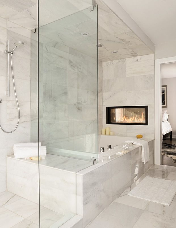 The shared wall between a master suite and the master bath is another great place for a dual fireplace. This bath was designed by none other than The Property Brothers.
