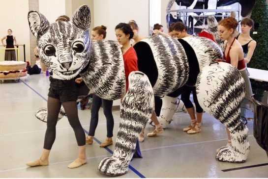 Behind the scene, the Cheshire Cat in a large puppet, on stage the dancers wear black and the illusion is incredible