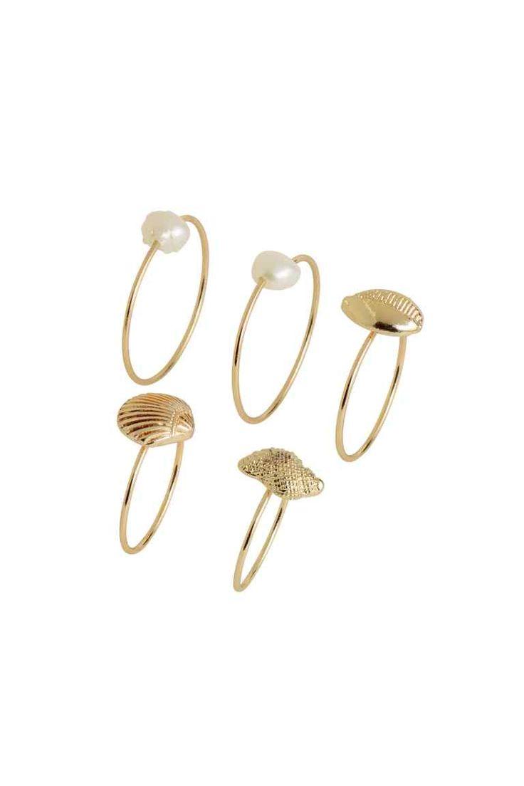 Lot de 5 bagues: Bagues fines en métal. Deux ornées d'une perle d'eau douce et trois avec décor en métal en forme de coquillage. Modèles de différentes dimensions, à porter sur la phalange supérieure ou inférieure des doigts.