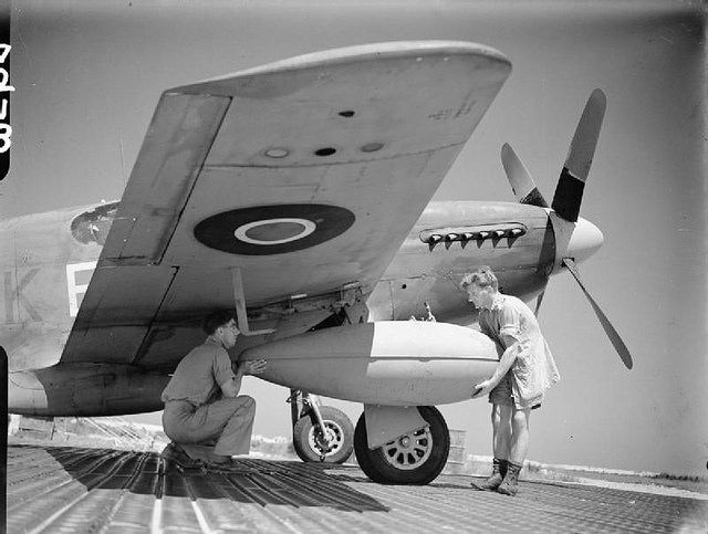 North American Mustang Mk.III -of No. 213 Squadron RAF at Biferno, Italy, loading long range tank for a mission in support of partisan forces in Yugoslavia.