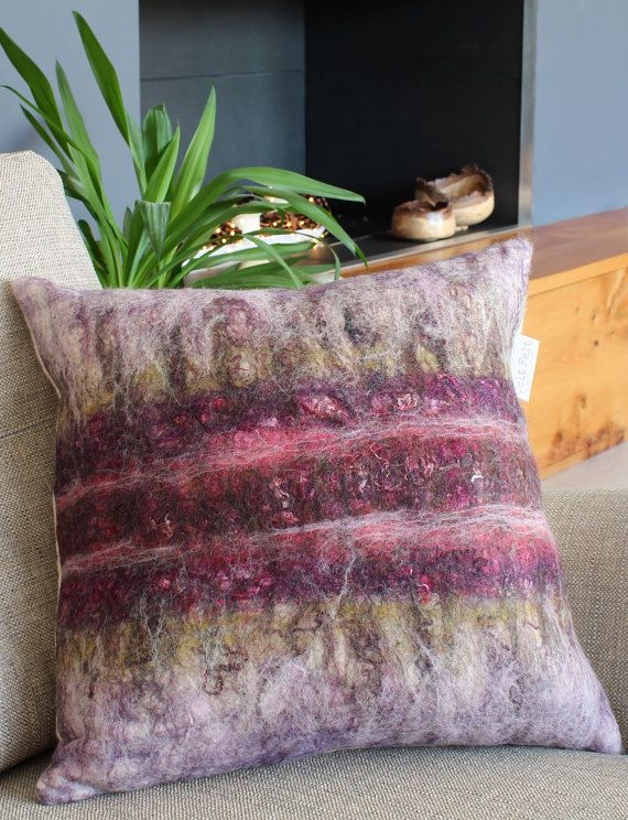 Speyside Collection - Heather cushion Handmade decorative cushion made using the ancient technique of felt making. This Speyside design is in the beautiful shades of purple and green that are found in wild Scottish heather. It has been hand felted using merino wool and shetland fibres with the addition of cotton scrim and silk threads. The back of the cushion cover is fastened with two decorative wooden buttons. The listing for this cushion includes a luxurious, feather filled pad. Size…