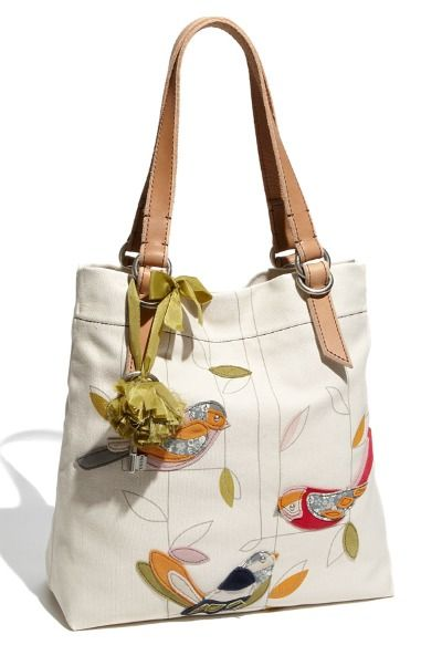 Whimsical bird appliqués lend charming detail to a roomy canvas tote suspended from leather handles with a cool, weathered look.      Magnetic-snap closure.     Interior zip, wall and cell phone pockets.     Cotton canvas with leather trim.     By Fossil; imported.