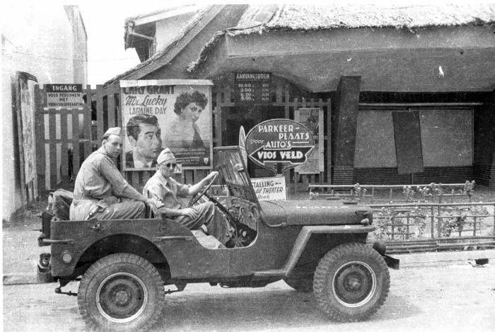 Jip Dengan Dua Orang Tentara Belanda Melintasi Muka Sebuah Bioskop Di Batavia Dengan Poster Film Mr Lucky 1943 Yang Dibintangi Cary Grant Jip Tentara Jeep