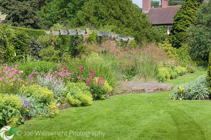 The Pergola Walk and adjacent herbaceous borders at Abbeywood Gardens, Cheshire - photographed in June