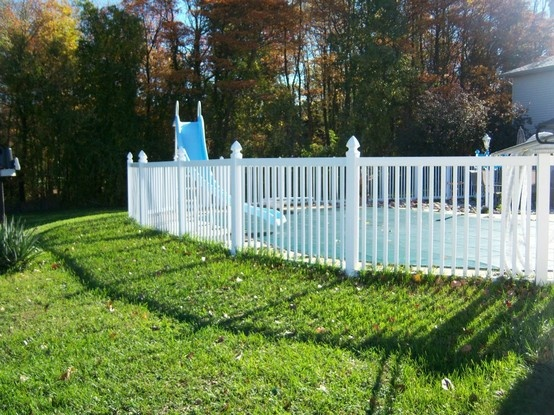 Colonial style white poly vinyl fence with Gothic post caps around pool
