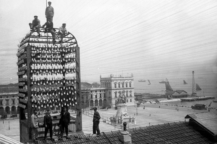 Sobre o Terreiro do Paço, operários na torre da Central Telegráfica, a 16 de maio de 1928. No dia seguinte, às 10H30, o Presidente Carmona e o Rei Afonso XIII, fazem o primeiro telefonema entre Lisboa e Madrid. Local: Praça do Comércio | Terreiro do Paço