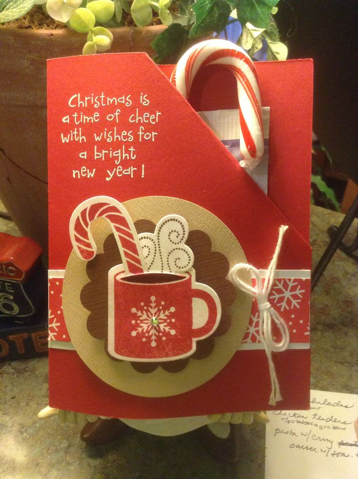 Holiday card that holds hot cocoa and a candy cane.