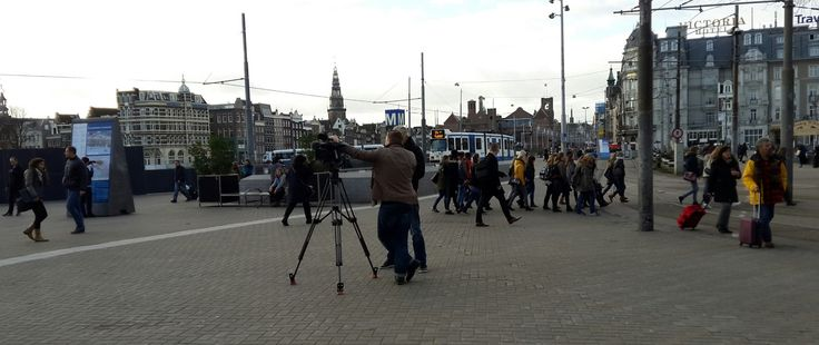 Two cameramen wait for me outside the Amsterdam train station.