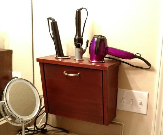 This wall-mount hair appliance storage unit allows for all hair care products to be stored in a convenient space on the wall and off the counter. All cords are nicely wound up on the inside door.