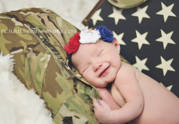 smiling newborn baby girl with her Daddy's Army uniform and dogtags