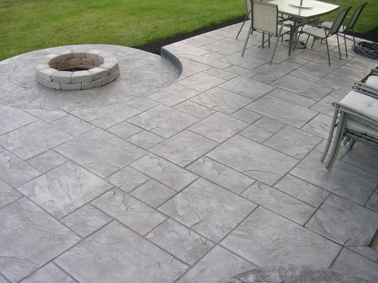 Minimalist Round Stone Fire Pit And Grey Stamped Concrete Patio In Spacious  Outdoor Space