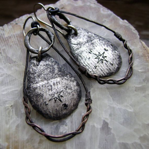 These unique mixed metal earrings feature a compass as the focal design so that you can always Find Your Way. I have textured the lightweight sheet aluminum by putting it through my roller mill with a vintage ribbon. This subtle texture has been enhanced by the directional compass I have stamped into the metal. These focals hang from soldered brass hoops that nestle inside of the hammered wire teardrop hoops. The variety of textures resulting from the different techniques used on the mixed…