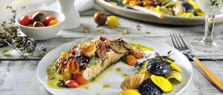 Een heerlijk visgerecht uit de Airfryer: gebakken zalm met gepofte tomaatjes en pesto, afgemaakt met gegrilde garnalen en gekookte pasta. Bekijk het recept.