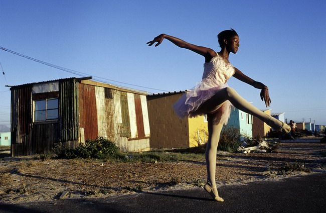 Noluyanda Mqutwana strikes a pose in 2000 outside her small family house in Khayelitsha, the biggest black township, outside Cape Town, South Africa. Noluyanda was one of about 200 underprivileged children in a program called Dance for All. The township has struggled with high unemployment, crime and high levels of HIV/AIDS. Photo © Anders Pettersson