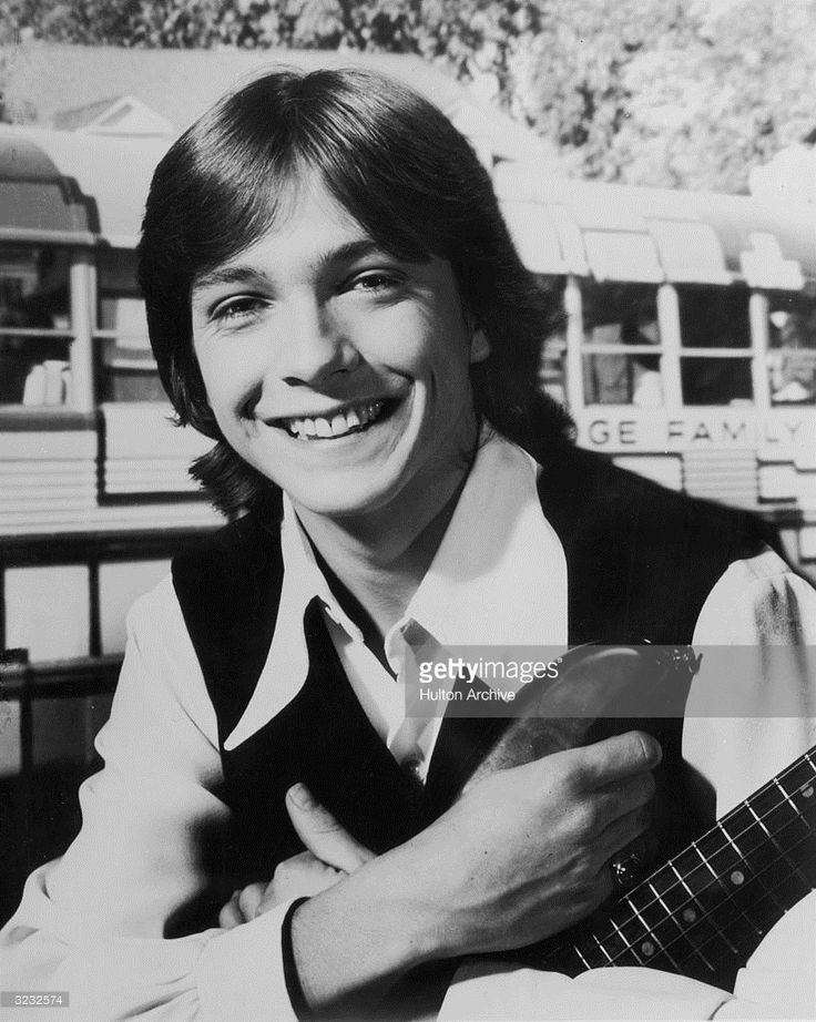 Headshot portrait of American pop musician and actor David Cassidy smiling and holding a guitar.