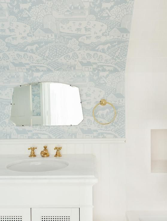 A simple white vanity sits under a sloped ceiling covered with a white and blue Farrow & Ball Gable Wallpaper.