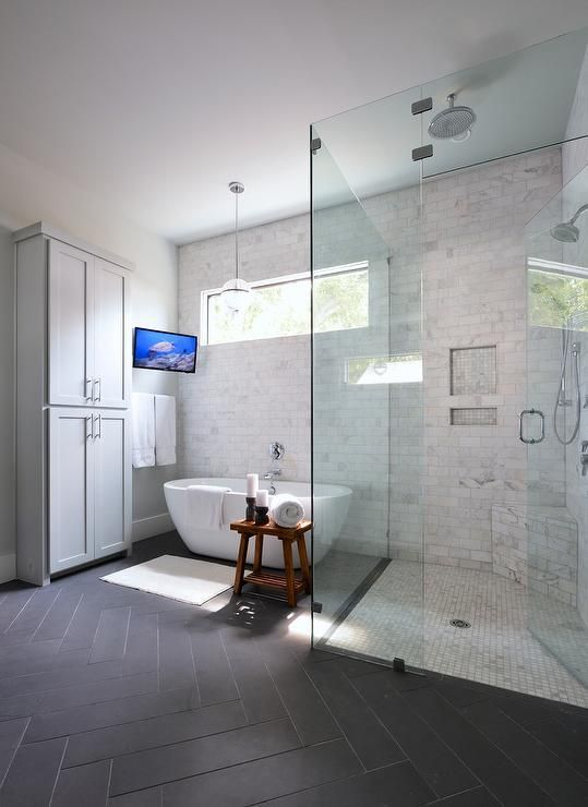 Transitional bathroom features a freestanding gray linen cabinet beside a tilted bathroom TV ...