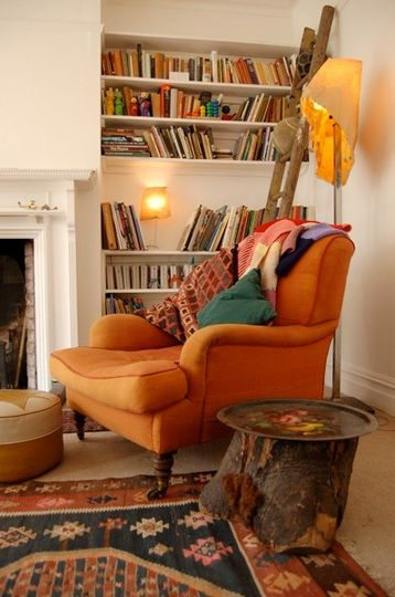 This space has a ton of elements I enjoy - orange, slightly faded multi-color rugs, white walls, and books, of course.