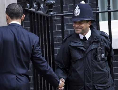 """This is the most powerful photo in the series. Remember they are not supposed to shake hands, but the two brothers couldnt resist the historic moment. The police guard never imagined in his wildest dream that he would usher a black American president into the British corridors of power."" #BarackObama"
