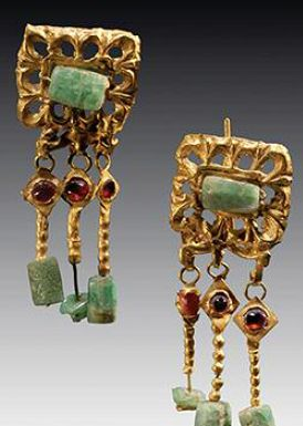 PAIR OF ROMAN GOLD, EMERALD, AND GARNET EAR PENDANTS from which hang three gold rods, a cabochon garnet on the top, and a rectangular emerald on the bottom of each. Ca. 3rd Century AD |