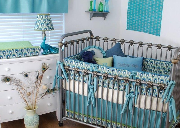 Peacock print fabric with aqua, green and navy in the custom crib bedding