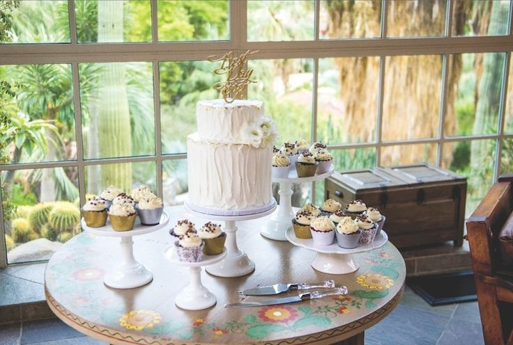 A petite wedding cake surrounded by individual treats lets couples have it all like this one from Over the Rainbow Cupcakes at Colony 29.