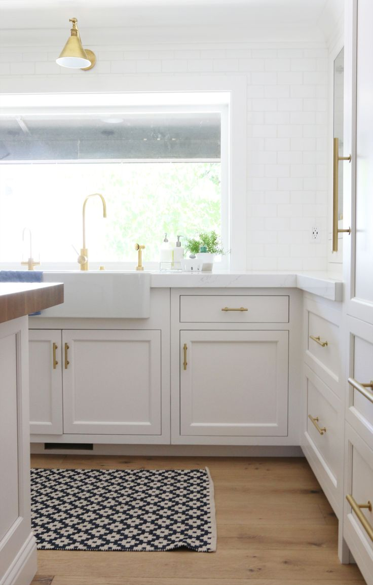 A kilim kitchen runner + brass fixtures in this white kitchen by Studio McGee studio-mcgee.com