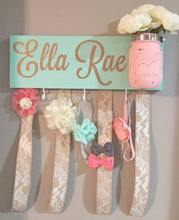 Display your little girls most treasured headbands and bows on this beautiful handmade bow holder. Each holder is hand painted mint. Names are added with a high quality gold glitter vinyl. And a hand painted pink mason jar is attached for decorative flowers or other accessories of choice. Flowers Not included.  Please leave name wanted for board in your notes at check out. We can add first and middle but the least amount of letters used will fill up the space on the board better :)  Each…
