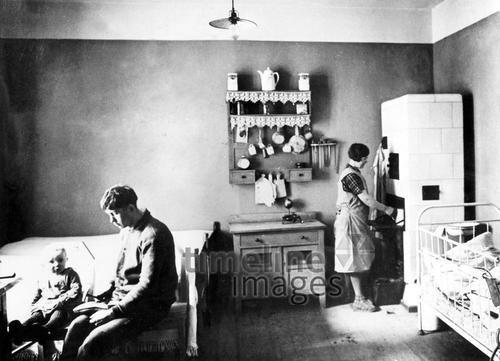Wohnraum einer Arbeiterfamilie in Berlin, um 1930 Timeline Classics/Timeline Images #1930er #1930ies #Arbeiterfamilie #Berlin #historisch #historical #schwarzweiß #Wohnen #Vater #Mutter #Kind