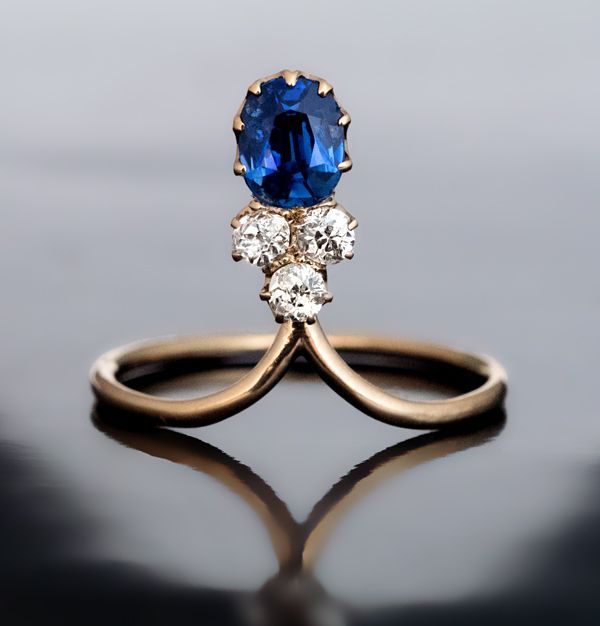 An Elegant Art Nouveau Antique Sapphire and Diamond Ring Russian, made between 1908 and 1917 The 14K rose gold ring is set with a blue sapphire (approximat