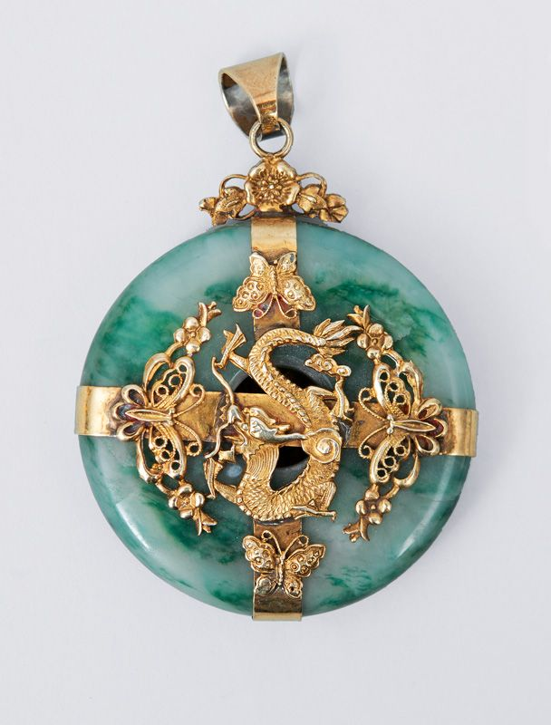 A big jade pendant with dragon mounting China, c. 1900. Bi-slice of jade enveloped by silver and gold plated metal in the centre with a dragon sourrounded by butterflys and blossoms. Unmarked. Diam.