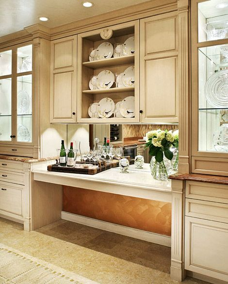 Lighted glass-front cabinets with mirrored interiors and a mirror backsplash on the bar reflect light in the pantry.