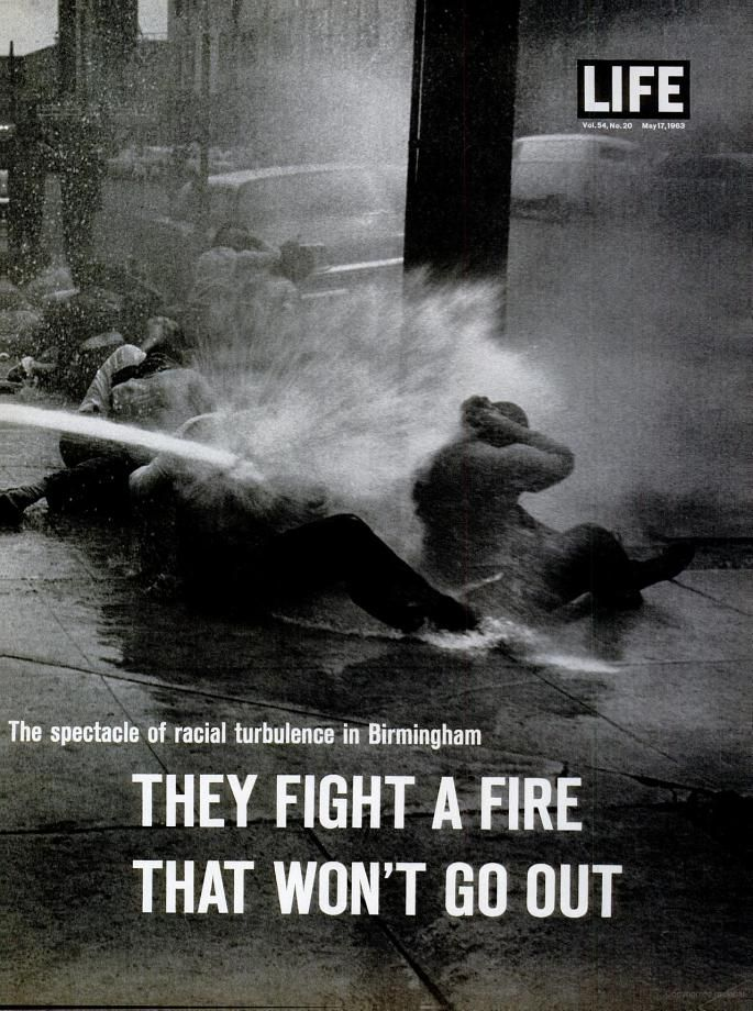 Non-violent civil rights demonstrators advocating for an end to racial segregation being hosed by mobilized local police, from the 17 May Life magazine article 'Ominous Spectacle of Birmingham: Racial Hatreds Approach a Flashpoint as a City Counters Negroes' Crusade with Fire Hoses and Fighting Dogs,' Birmingham, Alabama, United States, 1963, photograph by Charles Moore.