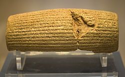 The Cyrus Cylinder.  Front view of a barrel-shaped clay cylinder resting on a stand. The cylinder is covered with lines of cuneiform text.  This documents the decision by Cyrus in 539 B.C. (or B.C.E. if you prefer) to allow a high degree of tolerance to different religions within the Persian Empire.