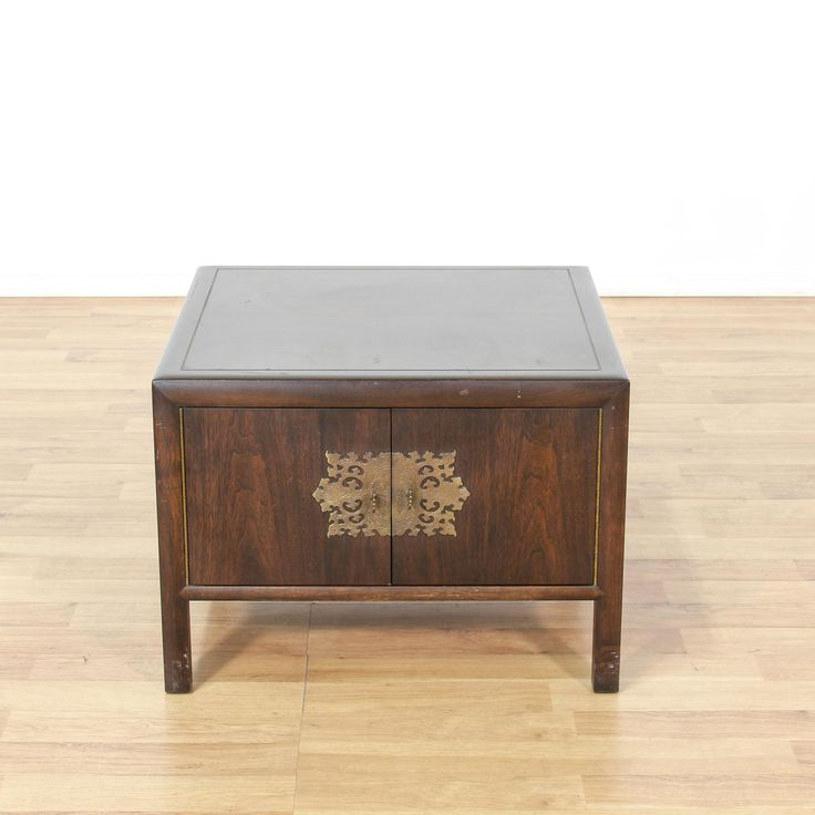 This end table is featured in a solid wood with a dark stain. This Asian style side table has a cabinet with ample storage space, shiny metal hardware, and beveled edges. Perfect for storing blankets! #asian #storage #cabinet #sandiegovintage #vintagefurniture
