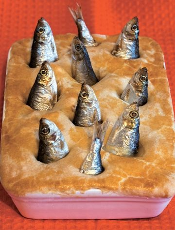 Stargazy pie is a traditional dish from Cornwall, England, featuring fish heads and tails arranged in a pie.