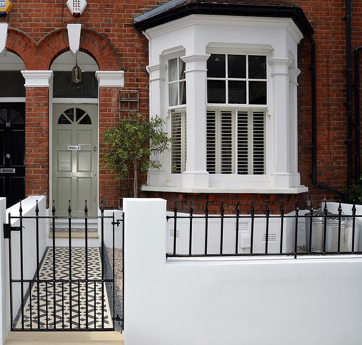 Plastered rendered front garden wall painted white metal wrought iron rail and gate victorian mosaic tile path in black and white scottish pebbles York stone