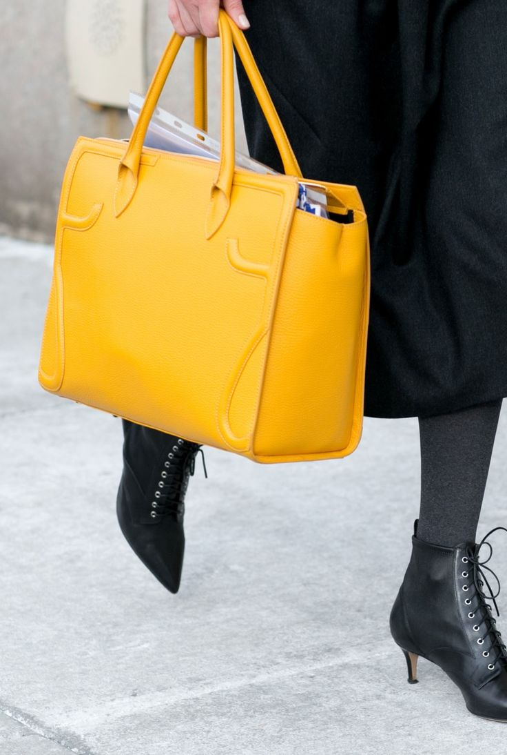 Love wearing black on black? Punch up your look with a bold yellow tote bag.