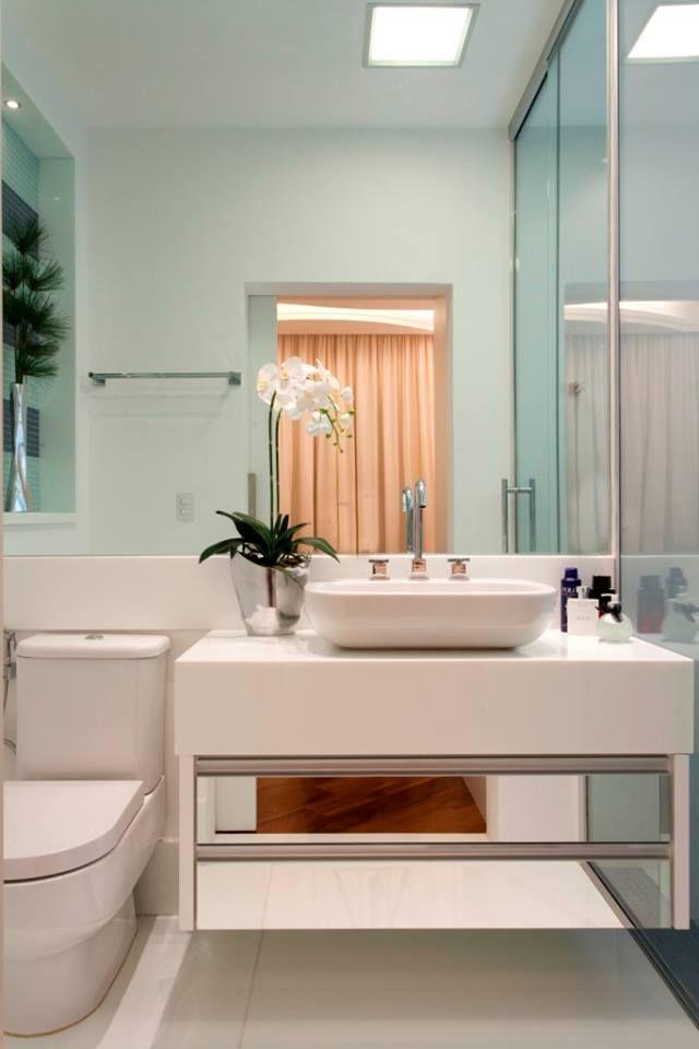 Lavabo com pedra branca e armário espelhado suspenso - Projeto Iara Kílaris