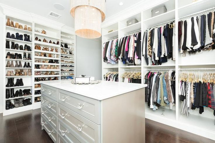 Wall of custom shoe shelves in a large master closet organizes shoes and accessories with an adjacent wall shelf displaying stacked racks of clothing.