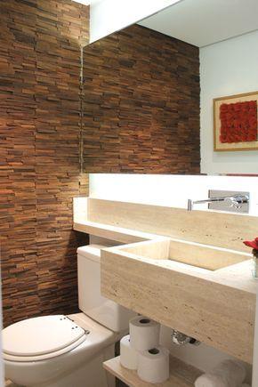 A cuba esculpida do lavabo, em mármore travertino romano bruto, é valorizada pelo mosaico de filetes de madeira.