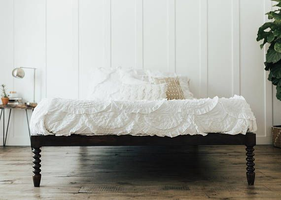 a sleek minimalist wood bedframe that features hand spun legs this frame is made out of solid wood and is perfect for any bedroom