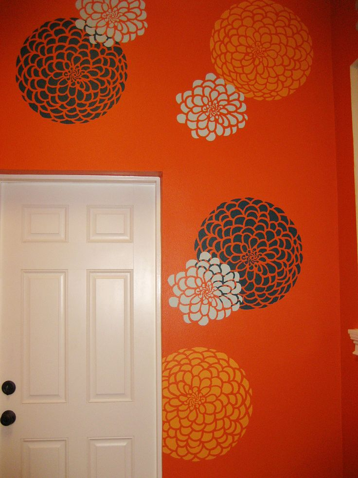 An orange laundry room stenciled with the Zinnia Grande Flower Stencil from Cutting Edge Stencils. http://www.cuttingedgestencils.com/flower-stencil-zinnia-wall.html