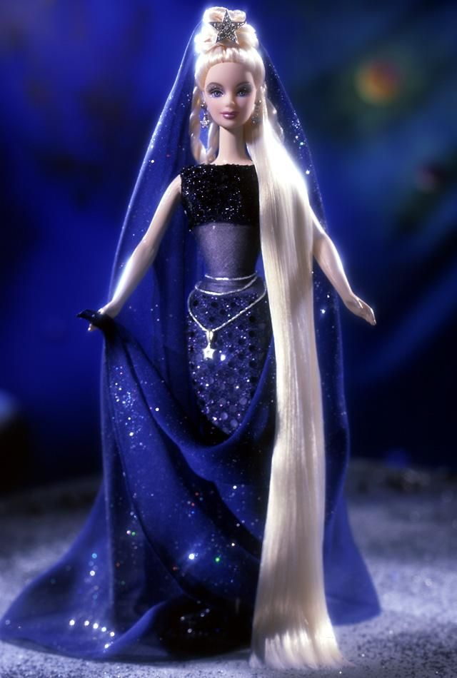 Barbie® doll shines as the brightest star in the night sky in her exquisite midnight blue gown with fitted bodice, sheer midriff and slim, full-length skirt. Barbie® doll's long blond hair is styled in an intricate coil then cascades to her feet. A silvery star crown accented with a long, flowing veil and dusted with glitter, shines atop her lovely head.