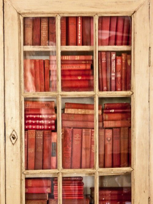 Red books in white cabinet