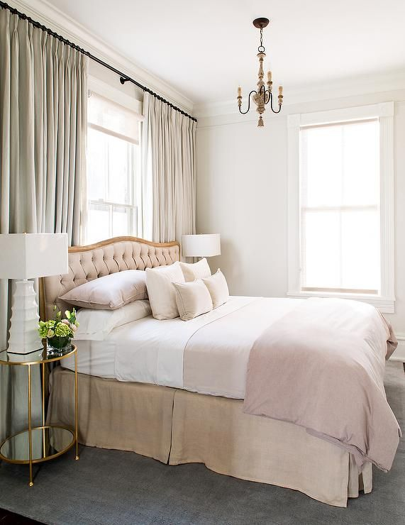 Sophisticated bedroom features a a dusty pink tufted headboard with wood frame on bed dressed in dusty pink bedding flanked by round brass and mirror nightstands topped with white pagoda lamps illuminated by a small French candle chandelier placed in front of windows dressed in gray curtains.