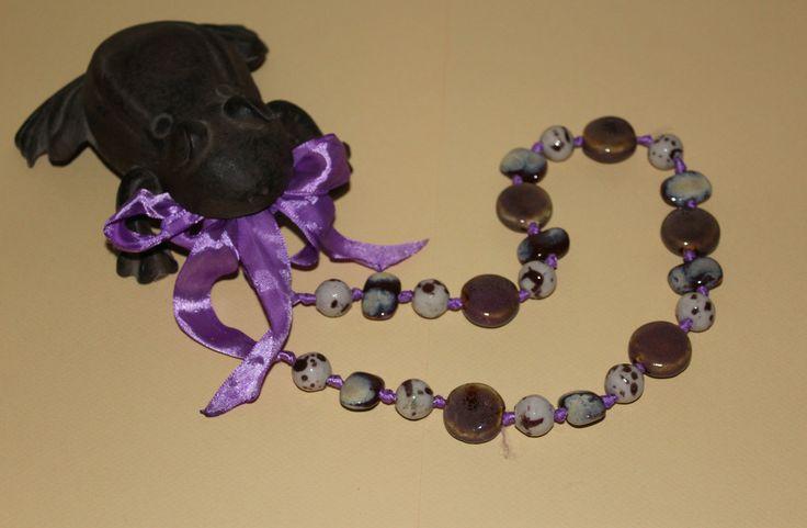 Élégant collier fantaisie, aspect craquelé, serti de perles de céramique, sur ruban de satin violet. Le ruban de satin à nouer permet de régler la longueur. De quoi égayer n'importe quelle tenue.